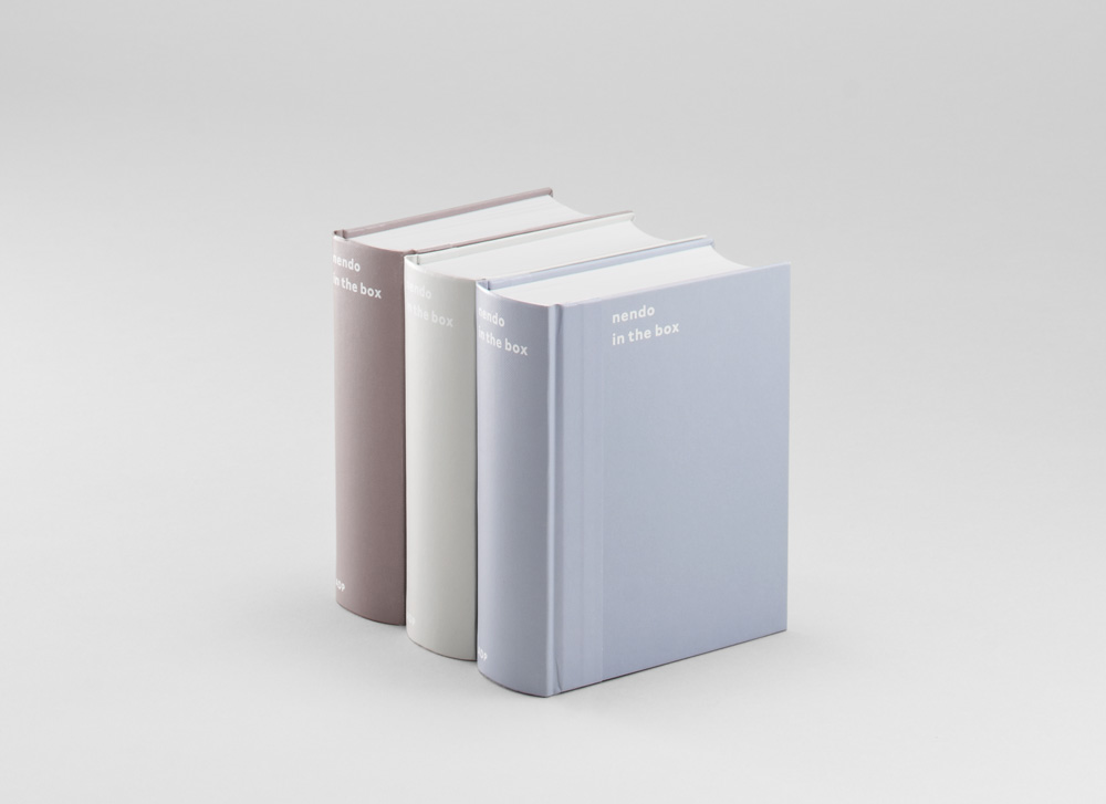 佐藤オオキ『nendo in the box』(2014年)。インテリアデザインスタジオ「nendo」の仕事を紹介する図録。クライアントへの提案の際にnendoがいつも作成する細やかな模型のサイズ感を、「厚くて小さい」本の佇まいで表現。テープのような背の部分の素材も、完成した模型を運ぶ際に使われる箱に使われる梱包用テープに想を得たもの。